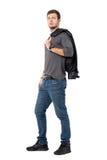 Vue de côté de veste de transport de jeune homme occasionnel au-dessus de l'épaule regardant l'appareil-photo Photos stock