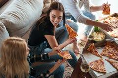 Vue de côté des amis mangeant de la pizza dans la maison Images libres de droits