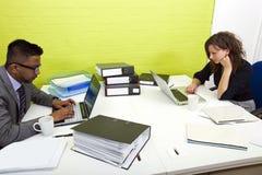 Vue de côté des collègues travaillant à leurs bureaux vis-à-vis de l'un l'autre photos stock