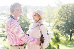Vue de côté des couples d'une cinquantaine d'années embrassant tout en regardant l'un l'autre en parc Photos stock