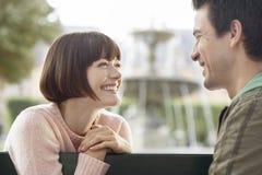 Vue de côté des couples de sourire sur le banc de parc Image libre de droits