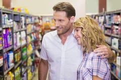 Vue de côté des couples occasionnels de sourire regardant l'étagère Images stock