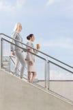 Vue de côté des femmes d'affaires abaissant des escaliers contre le ciel Photographie stock libre de droits