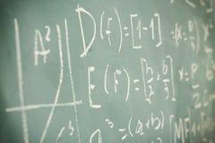 Vue de côté des formules et du calcul de maths écrits au-dessus du tableau Foyer sélectif Image libre de droits