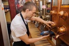 Vue de côté des grains de café de distribution de vendeur dans la cuvette au magasin Photos stock