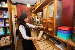 Vue de côté des grains de café de distribution de vendeur dans le sac de papier au magasin Photographie stock libre de droits