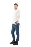 Vue de côté des jeans de port et des espadrilles de jeune homme occasionnel sérieux regardant l'appareil-photo Images stock