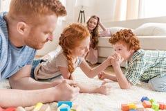 Vue de côté du frère et de la soeur jouant le bras de fer avec des parents tout près Photo libre de droits