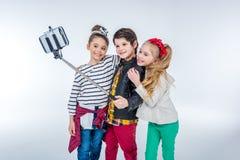 Vue de côté du garçon et des filles de sourire faisant le selfie Images stock