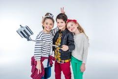 Vue de côté du garçon et des filles de sourire faisant le selfie Image libre de droits