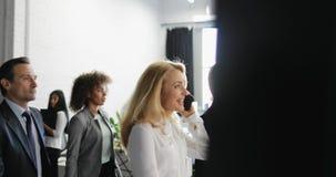 Vue de côté du groupe de gens d'affaires marchant dans l'immeuble de bureaux moderne avec la femme d'affaires parlant sur l'appel banque de vidéos