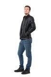 Vue de côté du jeune homme occasionnel dans les jeans et la veste en cuir souriant d'un air affecté à l'appareil-photo Images libres de droits