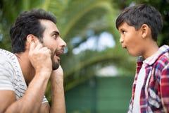 Vue de côté du père et du fils faisant des visages tout en jouant Images stock
