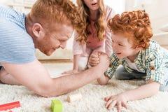 Vue de côté du père et du fils jouant le bras de fer avec la mère tout près Image libre de droits