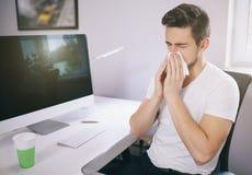 Vue de côté du patient& x27 ; employeur de s éternuement dans un tissu dans un bureau près de la fenêtre dans l'ordinateur indépe Photos stock