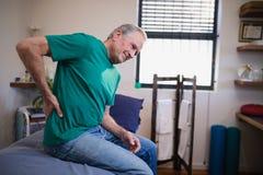 Vue de côté du patient masculin souffrant de la courbature tout en se reposant sur le lit photographie stock libre de droits