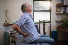 Vue de côté du patient masculin supérieur souffrant de la courbature tout en recherchant sur le lit photo stock