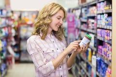 Vue de côté du sourire femme assez blonde regardant un produit Photographie stock