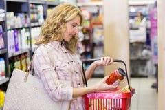 Vue de côté du sourire femme assez blonde regardant un produit Image libre de droits