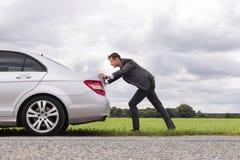 Vue de côté intégrale de jeune homme d'affaires poussant la voiture décomposée sur la route Photographie stock libre de droits