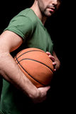 Vue de côté partielle de l'homme tenant la boule de basket-ball dans des mains Images libres de droits