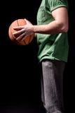 Vue de côté partielle de l'homme tenant la boule de basket-ball dans des mains Photographie stock