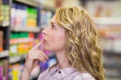 Vue de côté sur la femme assez blonde regardant l'étagère Photographie stock libre de droits