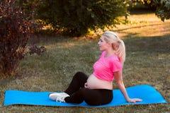 Vue de côté sur la séance enceinte dans la pose de lotus image libre de droits