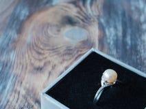 Vue de côté sur le bel anneau de perle dans la boîte noire sur le fond en bois Photo stock