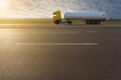 Vue de côté sur le camion de réservoir dans la tache floue de mouvement sur l'autoroute Photos stock