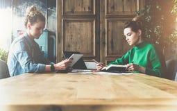 Vue de côté teamwork Deux étudiants s'asseyant dans un café à la table en bois Photos libres de droits