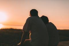 Vue de côté un ménage marié une silhouette se reposant sur un banc Photo libre de droits