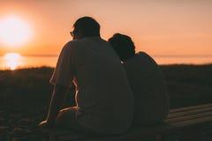 Vue de côté un ménage marié une silhouette se reposant sur un banc Photo stock