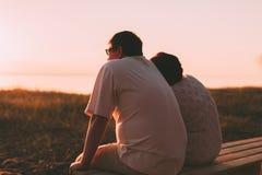 Vue de côté un ménage marié une silhouette se reposant sur un banc Image libre de droits
