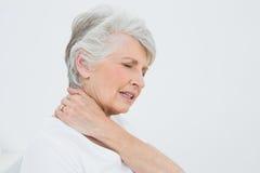 Vue de côté d'une femme supérieure souffrant de la douleur cervicale Images libres de droits