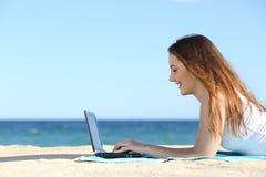 Vue de côté d'une fille d'adolescent passant en revue un ordinateur portable sur la plage Image stock
