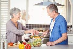 Vue de côté des couples supérieurs heureux préparant la nourriture Photographie stock libre de droits