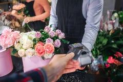 Vue de cabot de l'homme tenant la carte de crédit à disposition Il le donnent au fleuriste Flower que le vendeur a le thereminal  images libres de droits