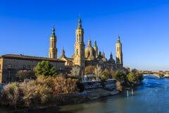 Vue de Cathédrale-basilique de notre Madame du pilier du pont en pierre de Puente de Piedra à Saragosse photographie stock libre de droits