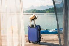 Vue de chambre à coucher avec le rideau en fenêtre et la valise de voyage avec le chapeau photographie stock