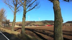Vue de champ contre deux turbines de vent et de petite ville en premier ressort Vue de voiture mobile en Pologne banque de vidéos