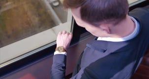 Vue de ci-avant Un jeune homme d'affaires dans un costume marche à la fenêtre et aux regards à la montre chère chic bureau banque de vidéos