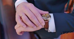 Vue de ci-avant Un jeune marié avec un homme d'affaires de bague dans un costume regarde la montre chère chic bureau clips vidéos
