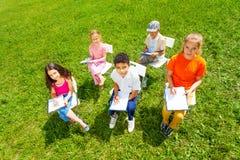 Vue de ci-dessus des enfants dessinant sur des presse-papiers Photo stock