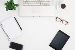 Vue de ci-dessus du bureau blanc avec le comprimé et le smartphone Images stock