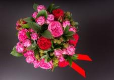 Vue de ci-dessus sur le bouquet élégant des roses roses et du ruban rouge Photographie stock libre de droits