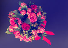Vue de ci-dessus sur le bouquet des roses roses et du ruban rouge dans une escroquerie Images stock
