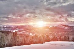 Vue de coucher du soleil en montagnes neigeuses, pente de ski Photographie stock