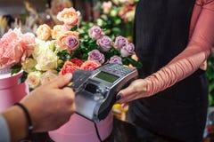 Vue de coupe de l'homme tenant la carte de crédit au-dessus du therminal d'argent Il paye des fleurs Jeune argent femelle de pris photos stock