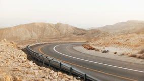 Vue de courbe vide de route goudronnée dans le désert de l'Israël 4K Chaussée dans le paysage antique de désert du Néguev Transpo banque de vidéos
